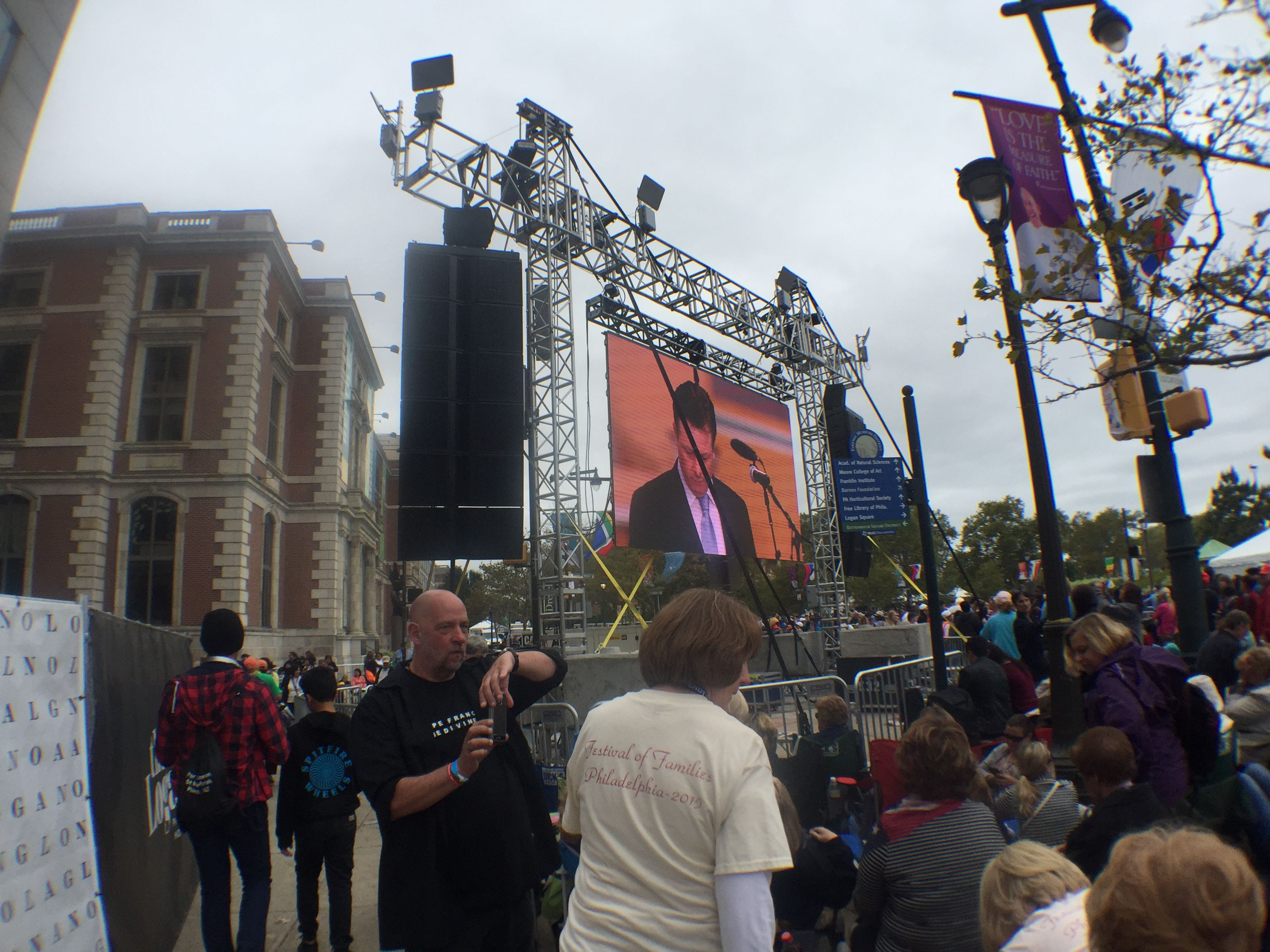 People gather by jumbotrons in Philly to watch the Mass.