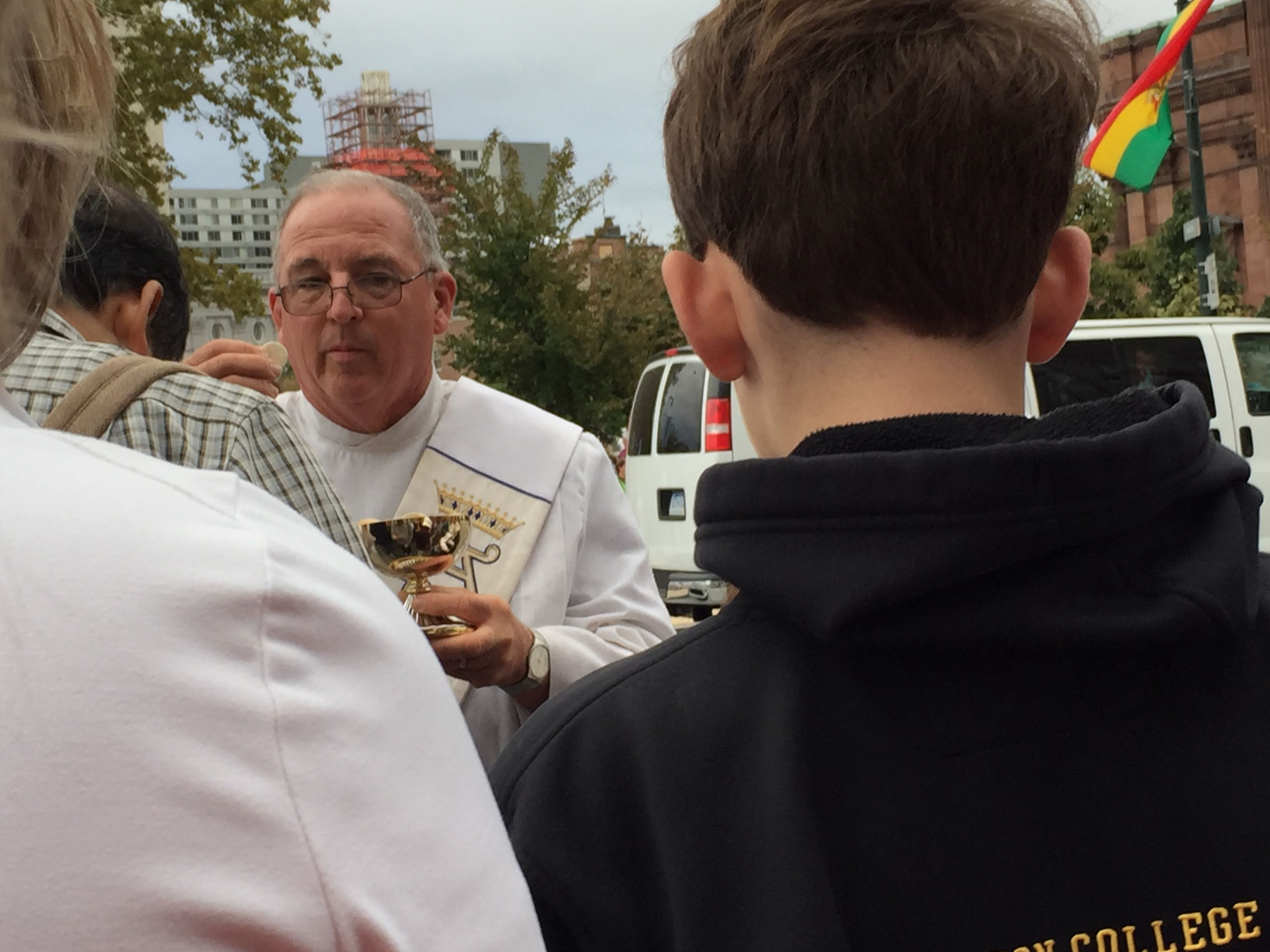 A priest hands out communion during the papal Mass in Philly.